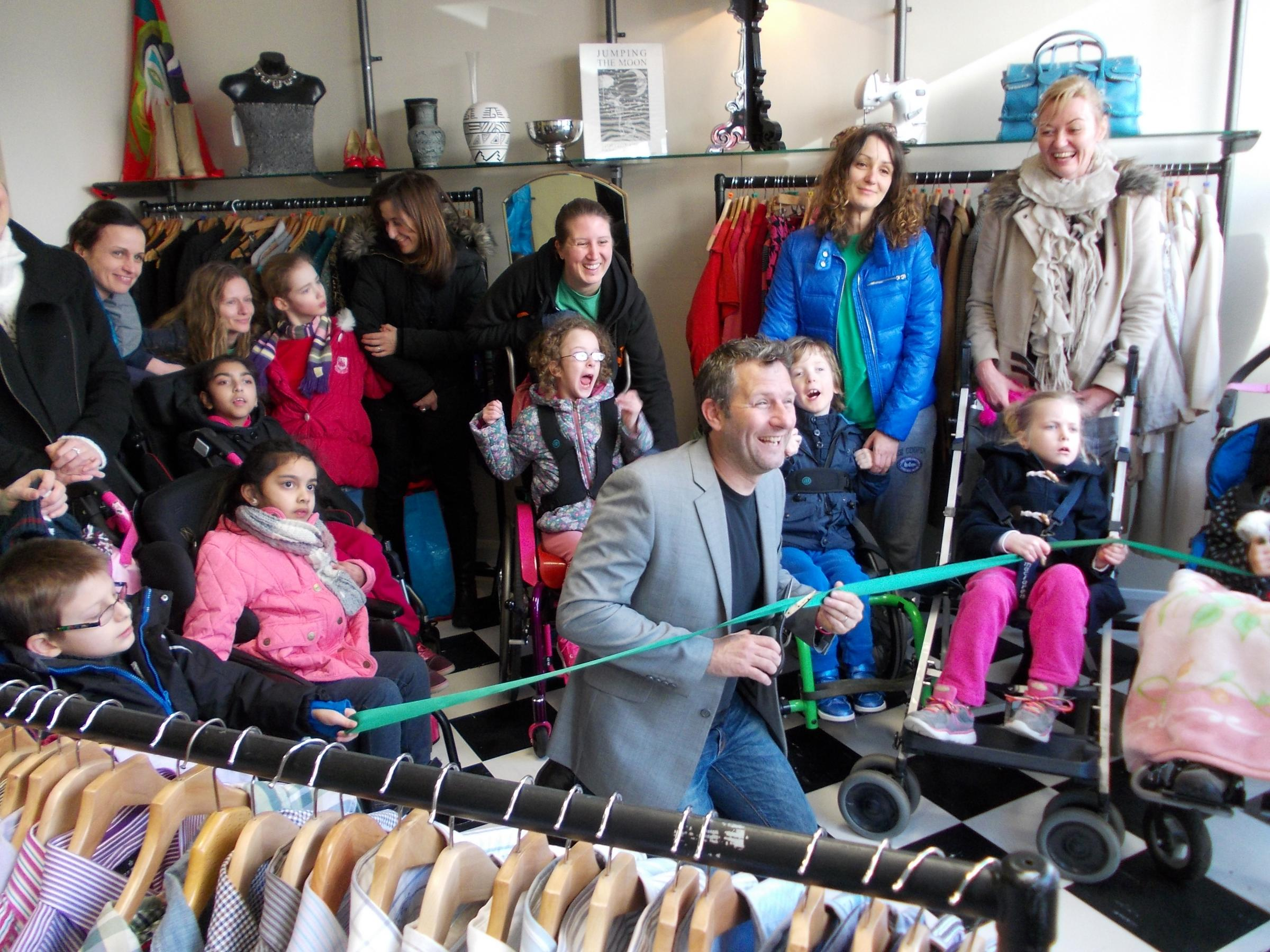 TV comedian Adam Hills was surrounded by students from the London Centre for Children with Cerebral Palsy as he cut the ribbon on its new store in Mus