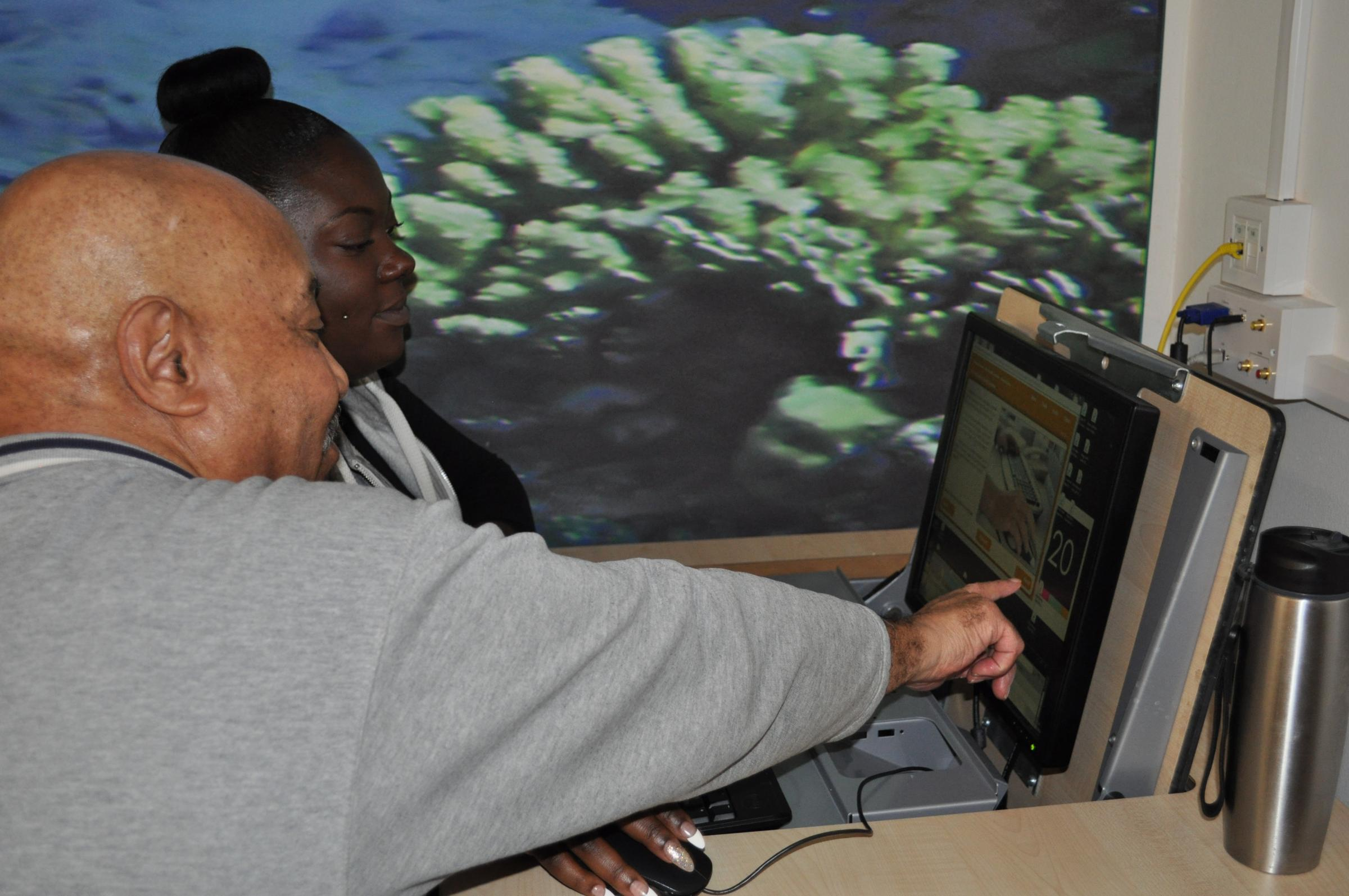 Volunteer Vanessa Logan shows Tyrone Clarke how to use a computer