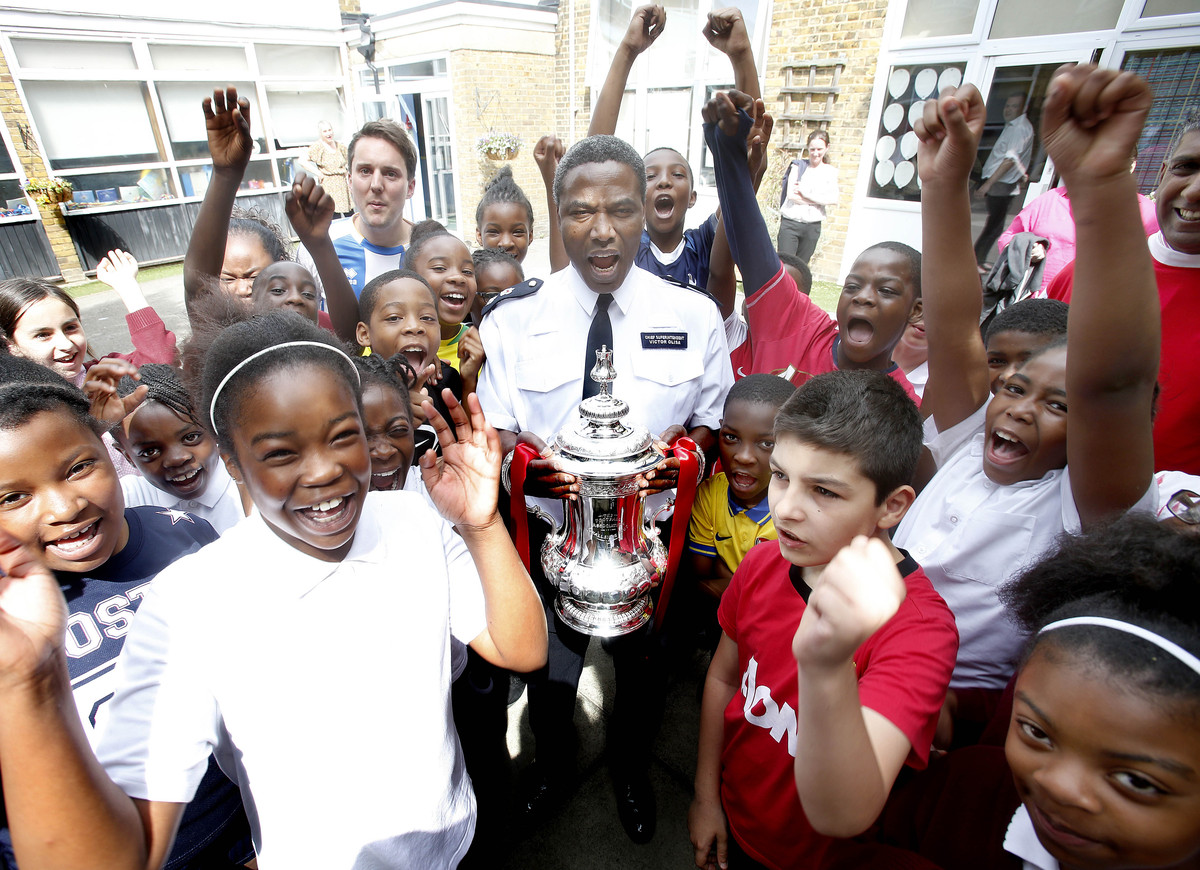 Tottenham's borough commander Victor Olisa holds the cup surrounded by schoolchildren who took part in the football tournament